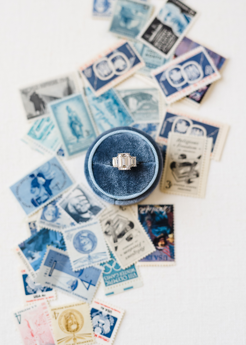 Flatlay of a blue wedding ring box with vintage stamps